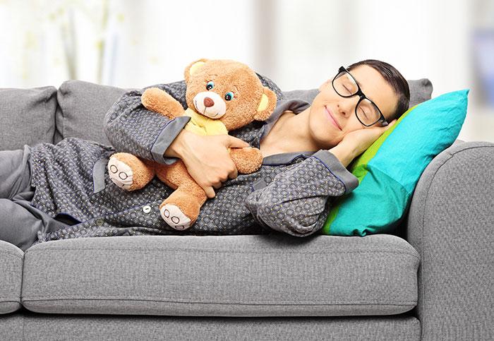 Boy sleeping on couch with teddy bear